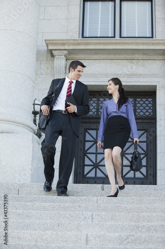 Caucasian business people walking down stairs