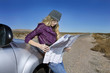 Caucasian woman reading map at roadside