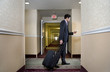 Asian businessman pulling suitcase in hotel
