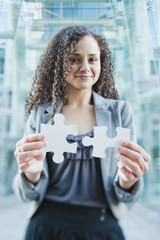 Caucasian businesswoman holding jigsaw puzzle pieces
