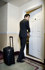 Asian businessman entering hotel room