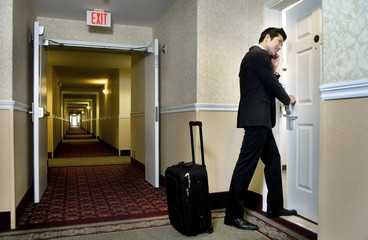 Asian businessman using cell phone and entering hotel room