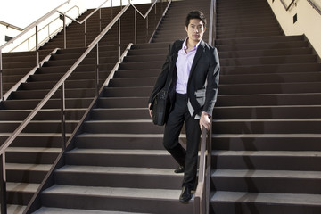 Asian businessman descending staircase