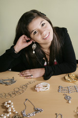 Hispanic teenager putting on jewelry