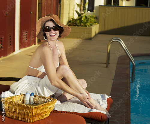 Caucasian woman sunbathing at poolside
