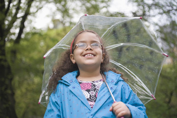 Hispanic girl standing in rain with umbrella