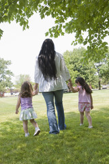 Hispanic mother walking in park with daughters