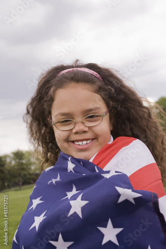 Hispanic girl wrapped in American flag