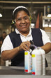 Hispanic woman with cans in factory
