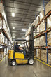 Hispanic worker driving forklift in warehouse