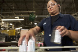 Hispanic worker picking up cans from assembly line