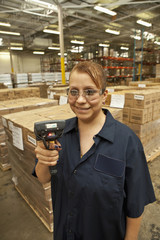 Hispanic worker with scanner in warehouse