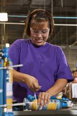 Hispanic worker assembling bottle in factory
