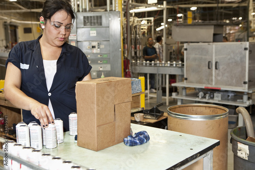 Hispanic worker packing boxes in factory