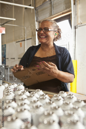 Hispanic worker packing boxes on assembly line