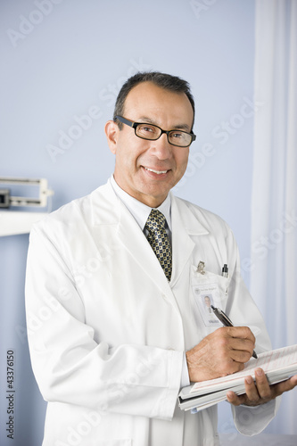 Doctor writing in medical record