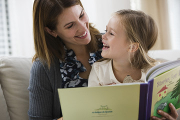 Caucasian mother reading book to daughter
