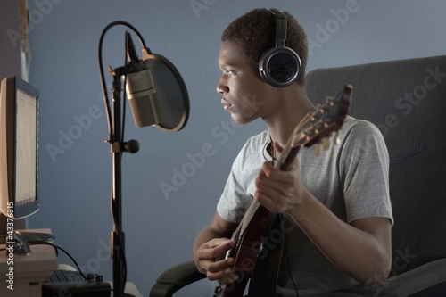 Mixed race boy strumming guitar and recording it on computer