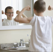 Caucasian boy flexing muscles in bathroom
