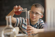 Caucasian boy doing experiment in chemistry class