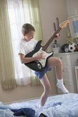 Caucasian boy standing on bed playing guitar