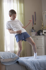 Caucasian boy standing on bed playing air guitar