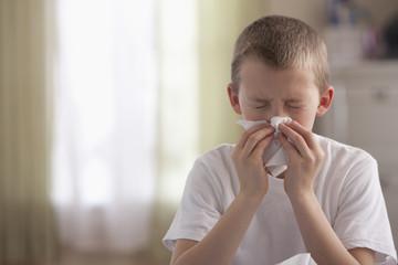 Caucasian boy blowing nose