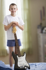 Caucasian boy standing on bed holding guitar