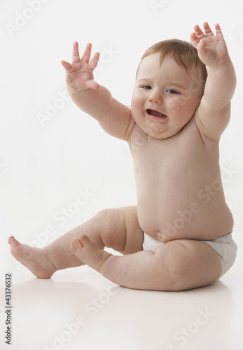 Chubby Caucasian baby boy with arms raised
