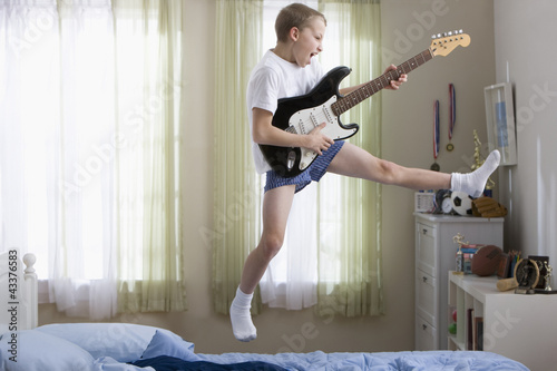 Caucasian boy jumping and playing guitar