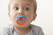Mixed race baby boy sucking pacifier