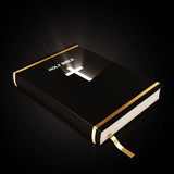Holy Bible isolated on black background with glowing rays