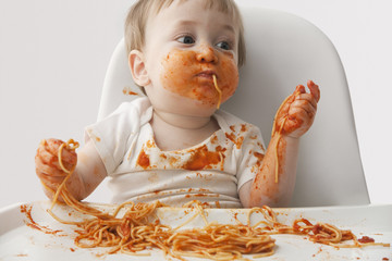Mixed race baby boy eating spaghetti