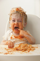Crying, mixed race baby boy eating spaghetti