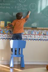 Caucasian boy drawing on blackboard in classroom