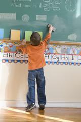 Caucasian boy erasing blackboard in classroom