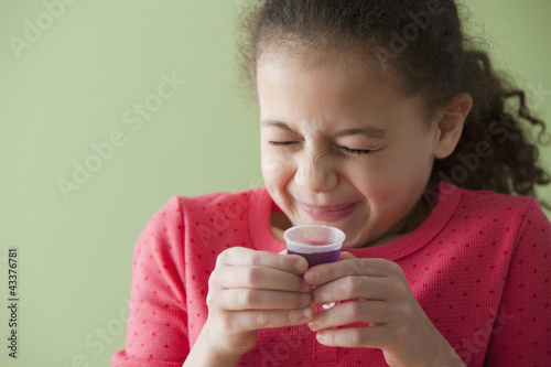 Hispanic girl taking cough syrup