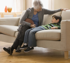 Caucasian grandmother holding football and talking to grandson