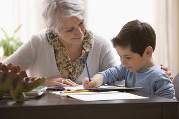 Caucasian grandmother helping grandson with homework