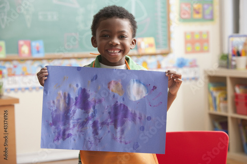 Black boy holding painting in art class
