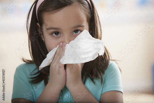 Caucasian girl blowing nose