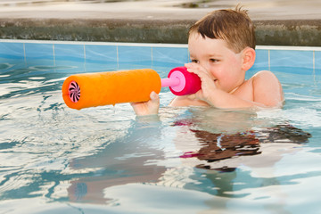 Child playing with water gun while swimming in pool