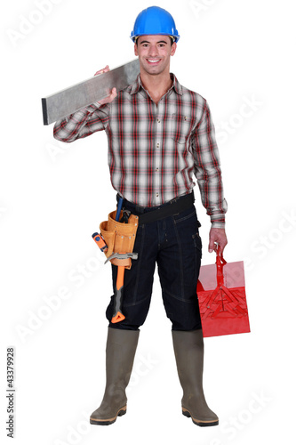 Worker carrying an aluminium plank and a toolbox
