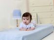 little child baby boy lying on the bed indoors in baby room