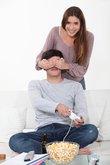 Couple fooling around whilst playing video games