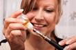 junge blonde Frau befüllt mit Liquid ihre elektrische Zigarette