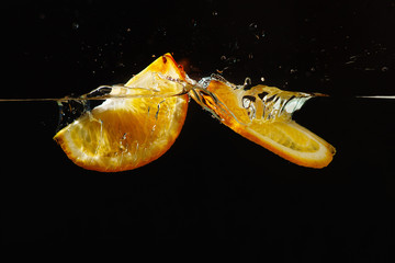 Two segments of fresh orange falling into the water with splash