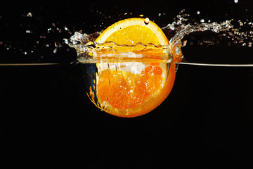 Sliced ripe orange falling into the water with a splash