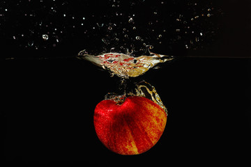 Halved ripe apple falling into the water with a splash