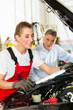 Älterer Mann und junge Mechanikerin am Auto